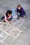 Girls playing with sidewalk chalk Royalty Free Stock Image