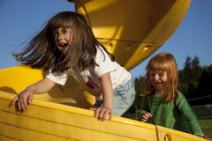 Girls Playing on Slide. Two smiling girls playing on yellow slide. Horizontal Stock Photo