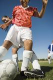 Girls playing soccer, one tackling another Stock Photography