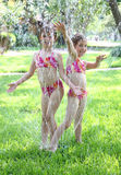 Girls Playing in Sprinkler Royalty Free Stock Images