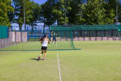 Girls playing tennis outdoors. Amateur tennis game stock images