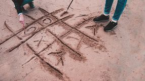 Girls playing tic-tac-toe on the beach. royalty free stock images