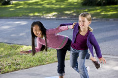 Girls playing together outside home Stock Photography