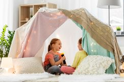 Girls playing with torch in kids tent at home. Childhood, hygge and friendship concept - happy girls playing with torch light in kids tent at home stock image