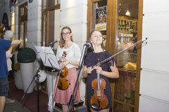 Girls playing violin outdoors stock photos