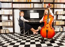 Girls playing on violoncello and the piano Royalty Free Stock Photography