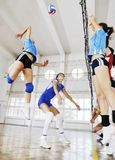 Girls playing volleyball indoor game Royalty Free Stock Photos