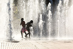 Girls playing in water jets. Silhouette of girls running and playing through vertical water jets stock images