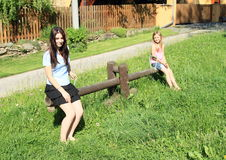 Girls playing on wooden swing Royalty Free Stock Images