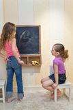 Girls in the playroom paint on the blackboard Stock Photo