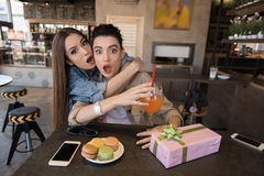 Girls are pleasantly amazed with open mouth in a cafe. Unbelievable, surprised young women looking at the camera Stock Photo