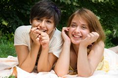 Girls pointing with finger on something smiling. Couple of girls enjoying their weekend on fresh air outdoors Stock Photography