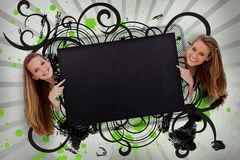 Girls pointing to black copy space with artistic black swirls Royalty Free Stock Photos