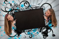 Girls pointing to black copy space on cursive design background Royalty Free Stock Image