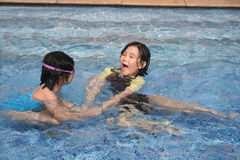 Girls in the pool. Two little girls playing happily in the pool Royalty Free Stock Image