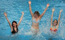 Girls in the pool. Three young girl jumps in the pool Stock Photography