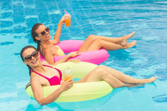 Girls at the pool. Beautiful girls in swimwear and sun glasses are drinking juice, looking at camera and smiling while swimming on swim rings in the pool Stock Photography