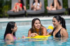 Girls At A Pool Party. Female friends at a pool party in the summer stock photo