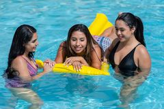 Girls At A Pool Party. Female friends at a pool party in the summer stock photos