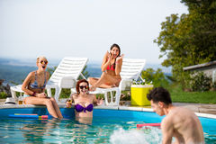Girls at pool surprised by their male friend in water Stock Photos