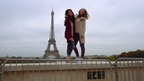 Girls pose for photography against Eiffel Tower. Paris, France - October 15, 2016: Two laughing girls in casual wear stand on stone fence, hug and pose for stock video
