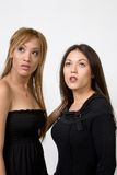 Girls Posing. Two  cute  and young girls in black dress looking up  over white background Stock Photos