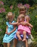 Girls posing in flower garden stock images