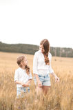 Girls posing in rye field. Two girl standing in rye field outdoors. Looking at each other. Childhood. Summer time Stock Photos
