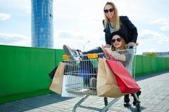 Girls posing in shopping trolley Stock Photo