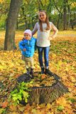 Girls posing standing on stump in autumn park. Happy childhood royalty free stock image