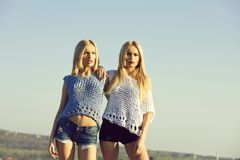 Girls posing on sunny day on blue sky. Girls or cute twin women, stylish female models, with long, blond hair in fashionable, knitted tops and shorts posing on stock photos