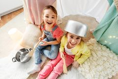 Girls with pots playing in kids tent at home. Childhood, hygge and friendship concept - happy girls with cooking pots playing in kids tent at home royalty free stock photography