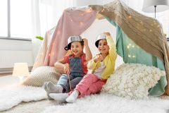 Girls with pots playing in kids tent at home. Childhood, hygge and friendship concept - happy girls with cooking pots playing in kids tent at home royalty free stock images