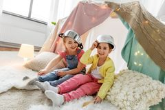 Girls with pots playing in kids tent at home. Childhood, hygge and friendship concept - happy girls with cooking pots playing in kids tent at home royalty free stock photo