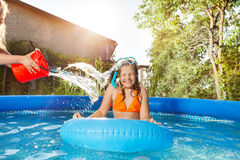 Girls pouring water from a red bucket in the pool Royalty Free Stock Photos