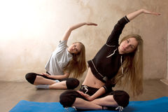 Girls practicing yoga in room Stock Photos