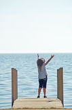 Girls Praising God On Dock. Young girl with her hands raised at the end of a dock on a large Great Lake in the middle of the day Stock Photo