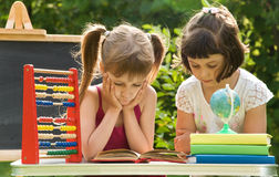 Girls prepare lessons on the nature and tired Stock Image