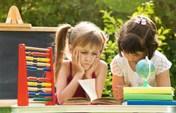Girls prepare lessons on the nature and tired Royalty Free Stock Photos