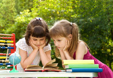Girls prepare lessons on the nature and tired Royalty Free Stock Photo