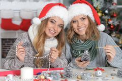Girls preparing for Christmas. Portrait of two beautiful young women in santa hats preparing for Christmas Stock Photography