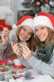Girls preparing for Christmas. Portrait of two beautiful young women in santa hats preparing for Christmas Stock Photos