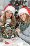 Girls preparing for Christmas. Portrait of two beautiful young women in santa hats preparing for Christmas Royalty Free Stock Photography