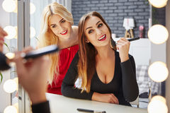 Girls preparing for ladies night. Two happy pretty ladies in front of mirror preparing for party Royalty Free Stock Photo