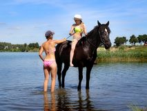 Girls are preparing for a photo shoot with the horse. Royalty Free Stock Image