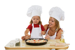 Girls preparing pizza. Woman and little girl preparing a pizza - isolated Stock Photography