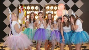 Girls are preparing to blow up a festive cracker with confetti. Cheerful portrait of a young bride friendgirls dancing in a fairy unicorn costume on hen party stock video