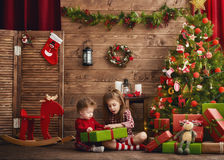 Girls with present. Merry Christmas and Happy Holidays! Two cheerful cute children girls with present. Kids hold a gift box near Christmas tree indoors Royalty Free Stock Photos