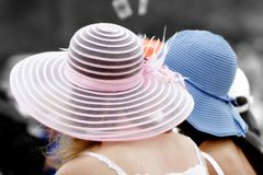 Girls in Pretty Hats. Young women wearing colorful hats watch an outdoor event together (shallow focus, color to BW effect royalty free stock photography