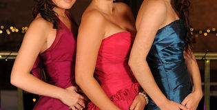 Girls in prom dresses. Bodies of three girls wearing colorful prom dresses stock photo